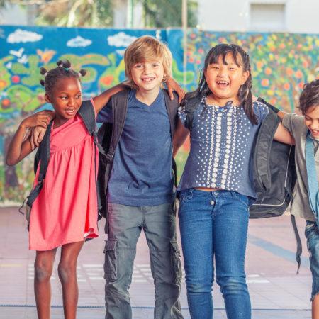 4 Kinder unterschiedlicher Ethnien umarmen sich