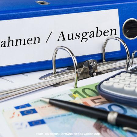 Thema Haushaltsberatungen: Ordner mit den Worten Einnahmen und Ausnahmen, ein Taschenrechner und Geld