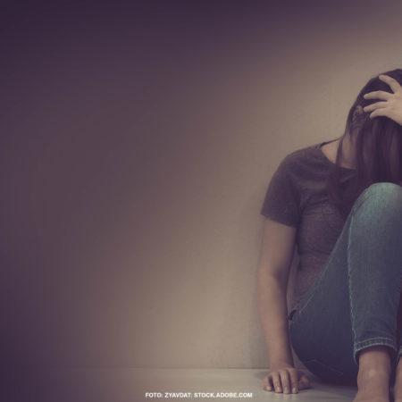 Häusliche Gewalt gegen Frauen durch Corona: Zusammengekauerte Frau am Boden. Sie verdeckt mit ihren Haaren und ihrer Hand ihr Gesicht.