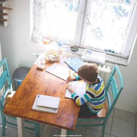 Ein Kind sitzt am Esstisch in der Küche und macht Hausaufgaben.