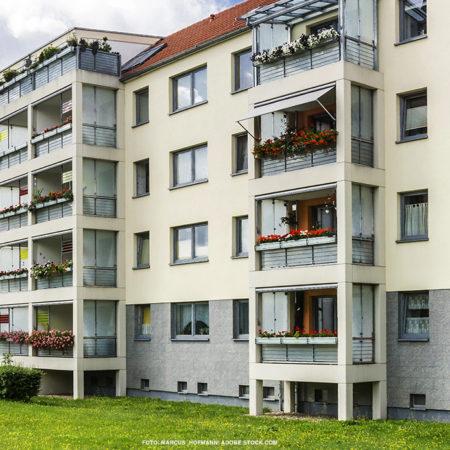 Ansicht von Wohnungsblock mit cremefarbener Wand und vielen Balkonen