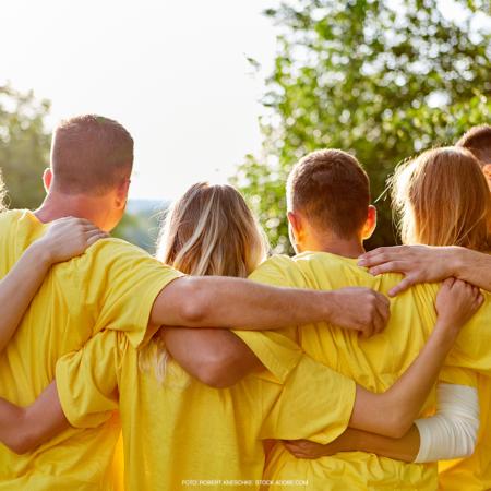 Drei Frauen und drei Männer halten sich glücklich im Arm, sie haben gelbe Tshirts an.