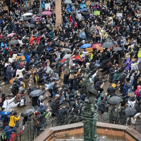Bild auf dem Demonstranten der Silent Demo am 05.Juni 2020 auf dem Römerberg kniend die rechte Faust in die Luft heben. Das soll an die Geste des Fußballspielers anlehnen, der das in Gedenken an den ermordeten US-Bürger George Floyd gemacht hatte.