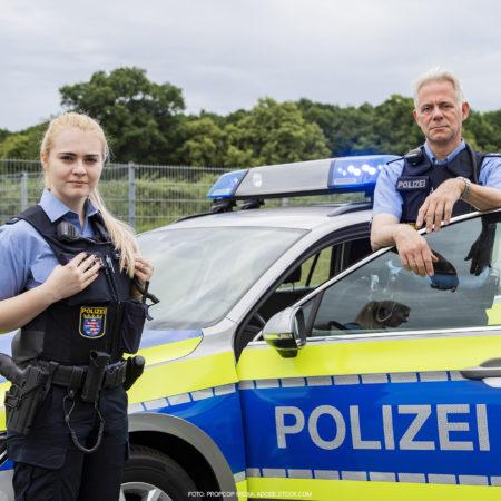 Zwei hessische Polizeibeamte, männlich und weiblich, in Uniform vor und am Polizeiauto