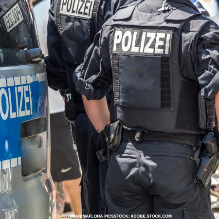 Zwei Polizisten mit Uniform und Polizeiauto