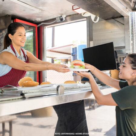 Verkäuferin gibt aus einem Foodtruck einer Kundin einen Hamburger.