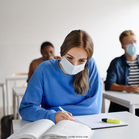 Kurs an einer Volkshochschule, im Vordergrund eine junge Frau mit Maske am Schreiben