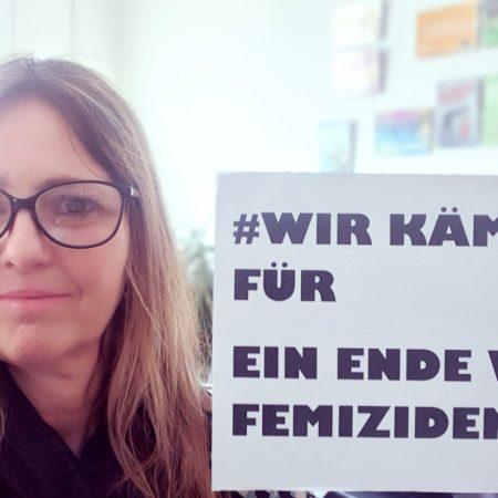 Die Stadtverordnete Stella Schulz-Nurtsch hält ein Schild hoch, auf dem steht: #wir kämpfen für ein Ende von Femiziden